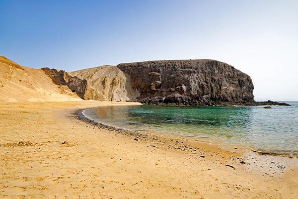 The golden sands and aqua coloured waters of Playa del Papagayo, Lanzarote, Canary Islands