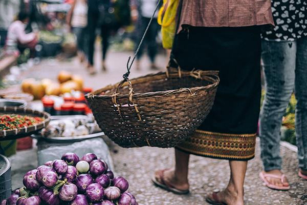 A woman carries a basket through a colourful food market in Luang Prabang, Laos
