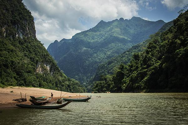Small wooden canoes line a small beach along a river with a stunning backdrop of lush green mountains in Laos