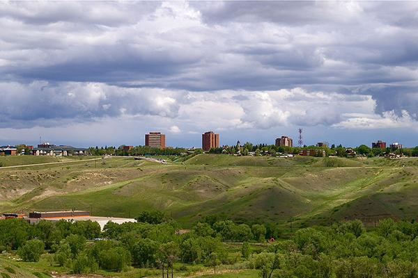 Skyline of downtown Lethbridge with a view of the iconic rolling hills of Alberta's prairies