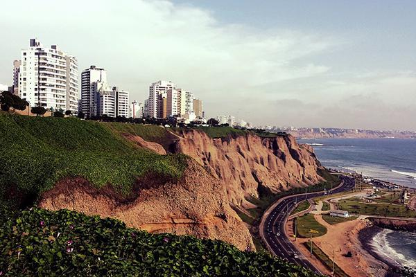 A coastal road winds along the Pacific Ocean below steep cliffs in Lima, Peru