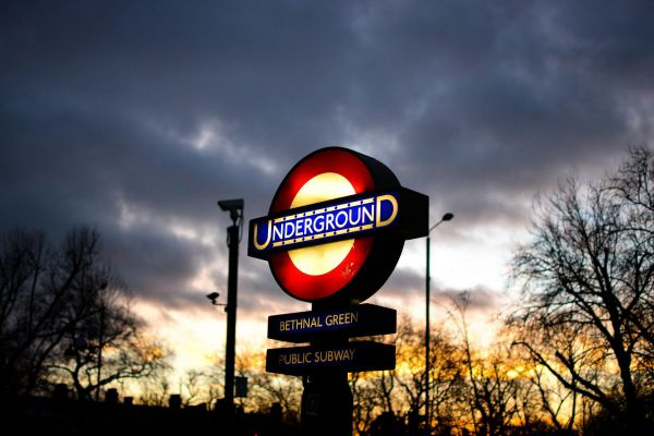 The iconic London Underground sign lit up at desk at Bethnal Green in the United Kingdom