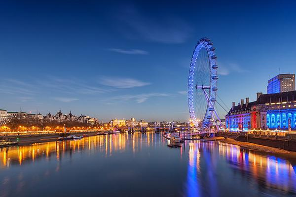 The London Eye and nearby buildings light up the Thames and the night sky of London, England