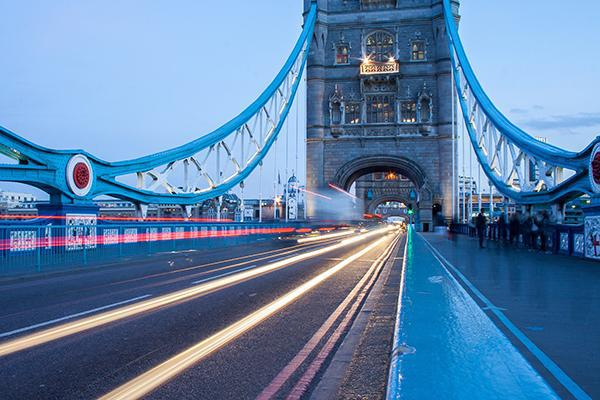 A long exposure of cars whizzing across the Tower Bridge in London, England