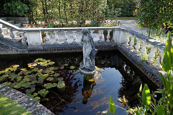 A pond with figurative sculpture water feature backed by a balustrade at Capel Manor College and Gardens, Bulls Cross, Enfield, London, England.