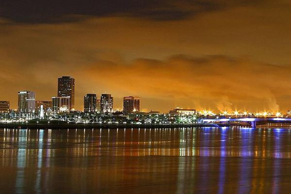 The city lights reflect off of the ocean's waters in Long Beach, California