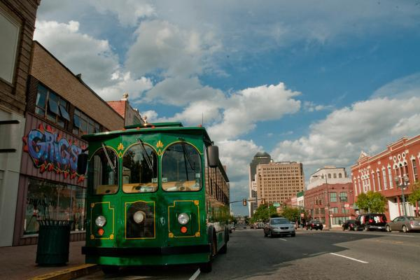 A green tour bus awaits passengers in downtown Shreveport, Louisiana