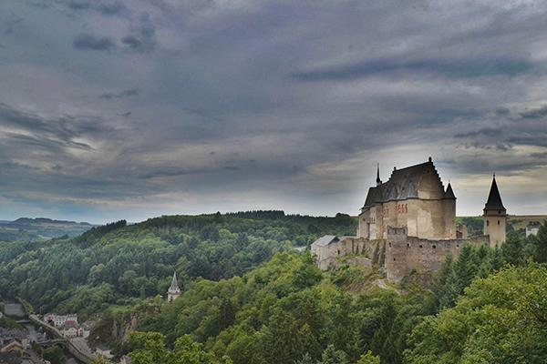 A castle stands high above the trees on a moody day in Luxembourg