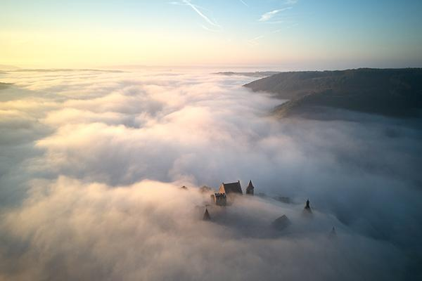 A castle in the clouds majestically standing above Luxembourg