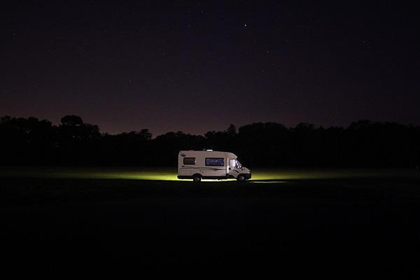 A lone RV lights up the night in Lyndhurst, United Kingdom