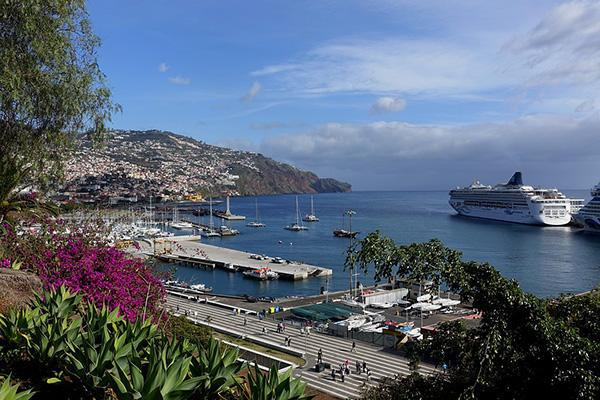 Ships and sailboats sit in the colourful port of Madeira, Portugal