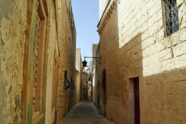 A narrow, medieval lane between stone buildings in Malta