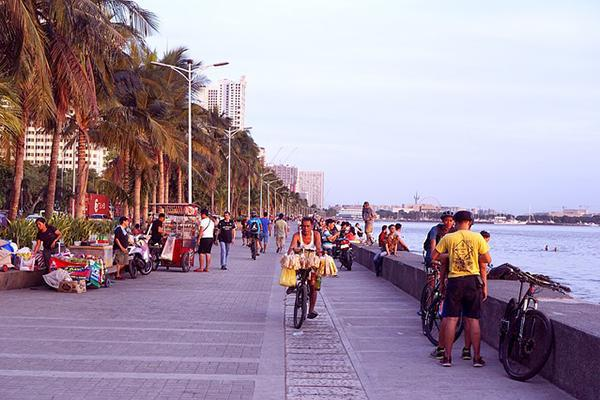 People going about their lives on the boardwalk in Manila Bay, Philippines