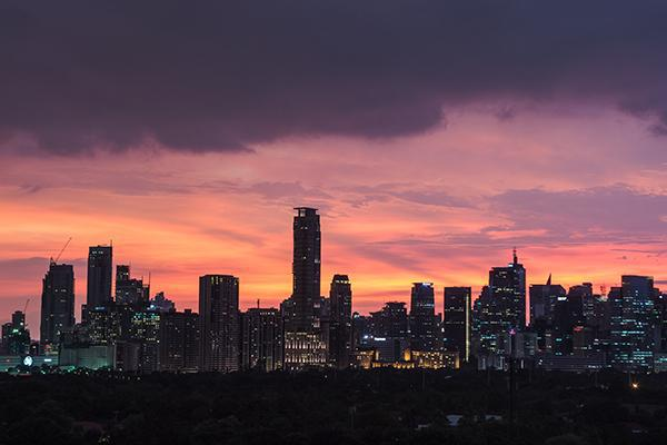 The skyline of Manila backlit by a dramatic sunset in the Philippines