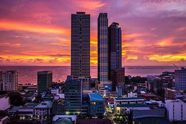 The sun sets behind the crowded skyline of Manila Bay, Philippines