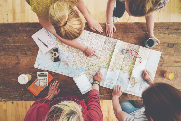 A group of friends plan a motorhome road trip itinerary.
