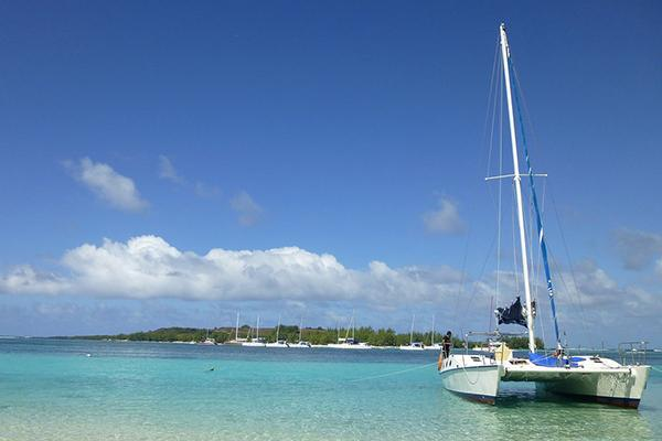 A catamaran sits on the turquoise blue waters of Mauritius