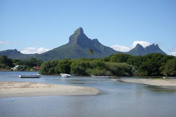 Lush green mountains backdrop a sandy lagoon in Mauritius