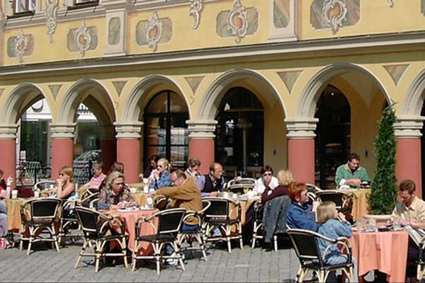 People dining out al fresco at an outdoor cafe in Memmingen, Germany