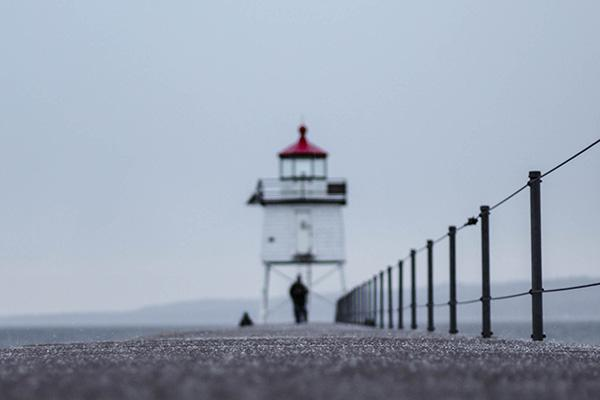 A pier leads out to a man standing in front of a lighthouse in Duluth on shore of Lake Superior