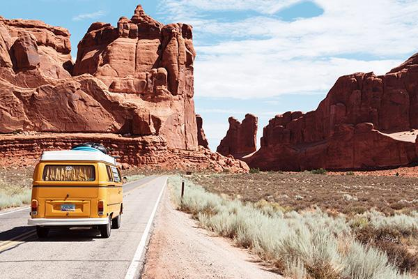 A vehicle drives amongst the red rock formations of Arches National Park, Utah