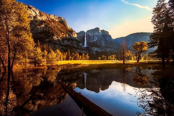 A mountain stands tall above a lake in Yosemite National Park, California