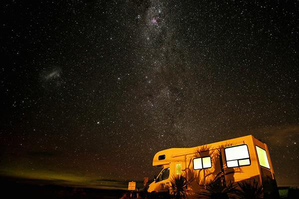 A motorhome parked up and glowing beneath the starry night sky in New Zealand