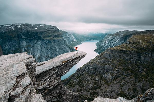 An intrepid traveller stands out on a jutted rock overlooking the spectacular and iconic scenery of mountainous Norway