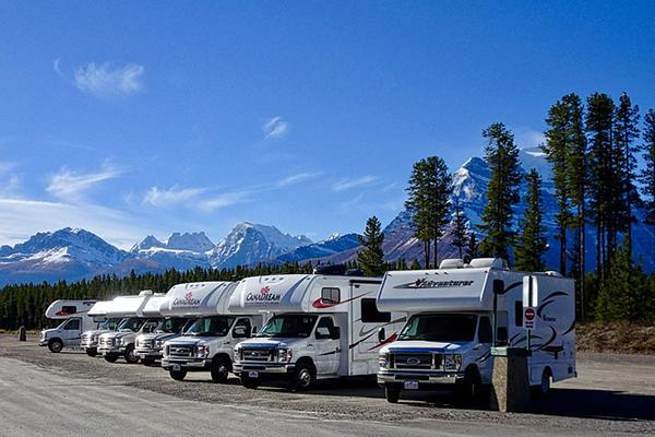 Motorhomes parked up beside each other with mountains in the background