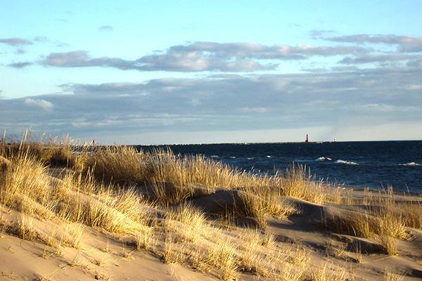 The sun shines down on the sandy shores of Lake Michigan in Muskegon