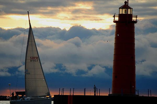 A sailboat floats next to the lighthouse at Pere Marquette Beach in Muskegon, Michigan at sunset