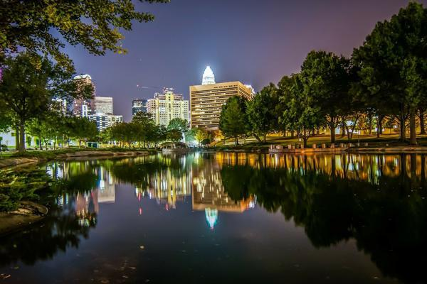 The city lights reflect off a body of water in a park in Charlotte, North Carolina