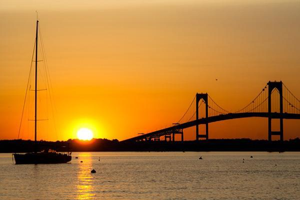 The setting sun paints the sky orange over the Claiborne Pell Bridge in Newport, Rhode Island