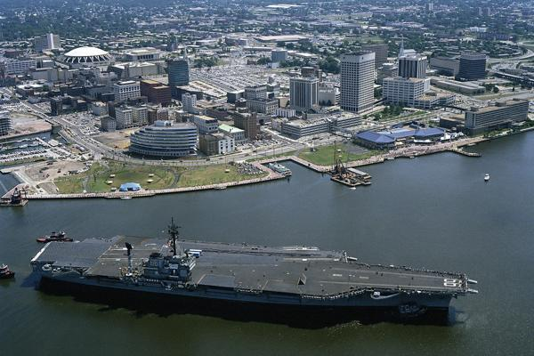 A United States Navy aircraft carrier is helped out of the Norfolk Harbor by two tugboats