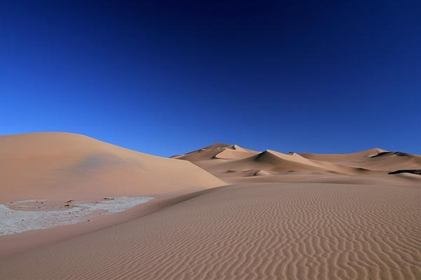 The desert sands of Algeria contrast brightly against the clear blue sky