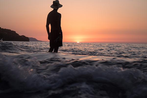 A man wades in the sea to watch a beautiful sunset in Algeria