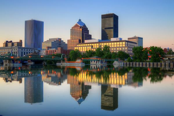 The Rochester skyline reflects off the still waters of the Genesee River in New York.