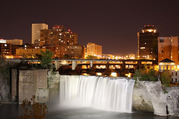 Water rushes over the edge of High Falls at night in Rochester, New York.