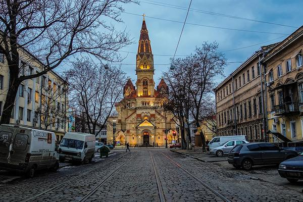 Cable car tracks with buildings and parked cars on either side lead toward an illuminated church in Odessa, Ukraine