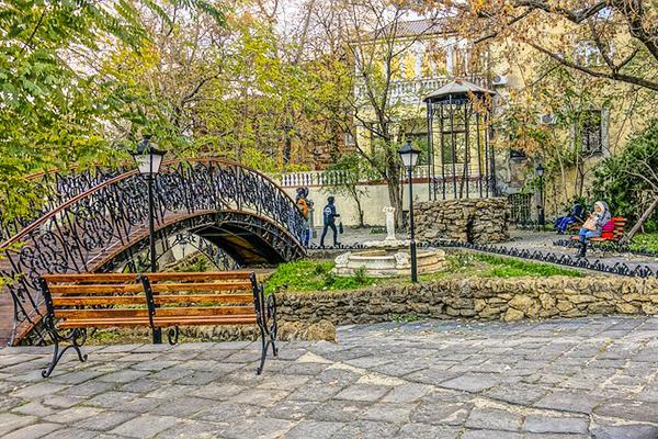 A rounded bridge, lanterns and leafy trees set the scene at a park in Odessa, Ukraine