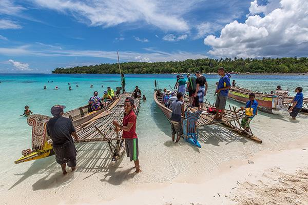 People load wooden canoes along the beach in Papua New Guinea