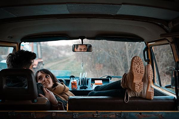 A couple cuddles in the cab of a campervan parked on the side of a road