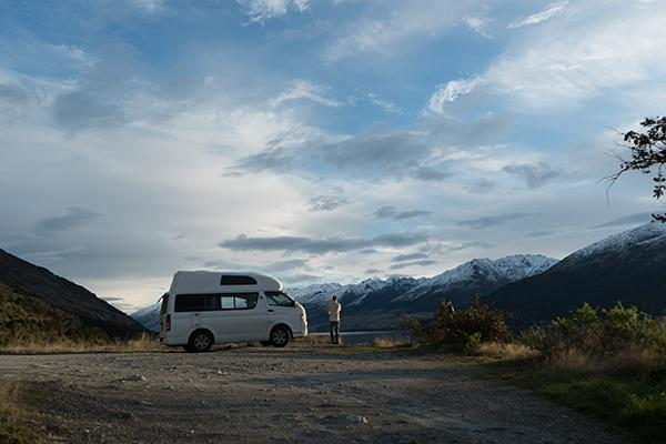 Travellers exit their campervan to admire the scenery of Lake Wanaka