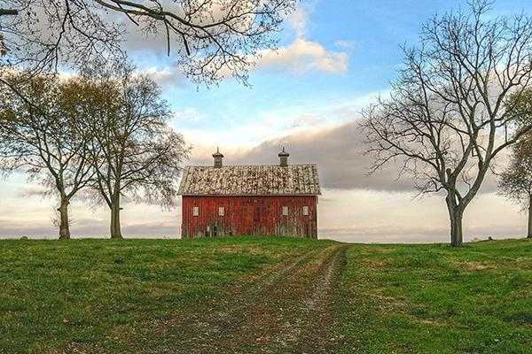 A red farmhouse on a rural field in autumn in Lancaster, Pennsylvania