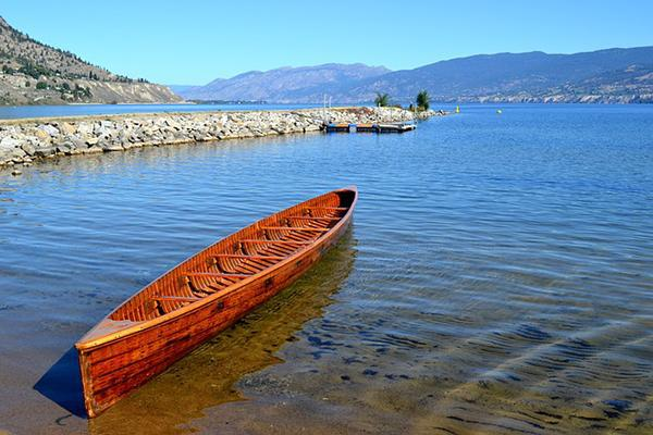 A war canoe sits on the shore of the Okanagan Lake in Penticton, British Columbia, Canada