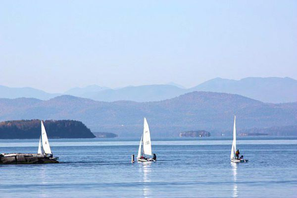 Three sailboats glide across the waters of Lake Champlain with small mountains off in the distance