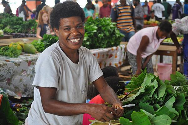 A local woman smiles as she runs her vegetable stand in Port Vila, Vanuatu