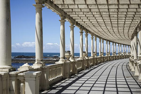 The sun shines through the white columns of a beautiful seaside structure in Porto, Portugal