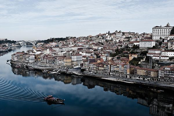 A boat glides through the Douro River Estuary, alongside the buildings of the city of Porto, Portugal