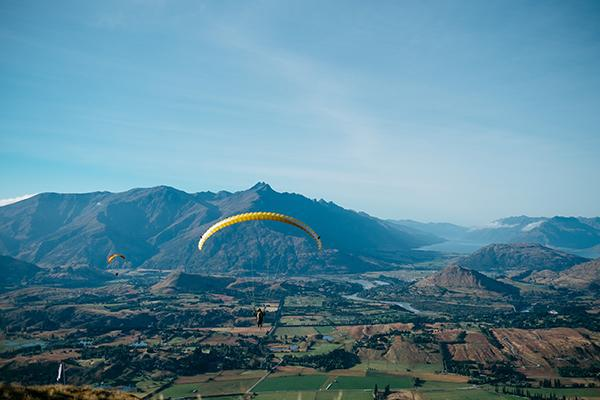 Two parasailers glide over Queenstown, New Zealand